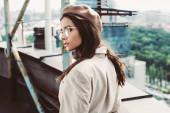 elegáns gyönyörű modell pózol bézs öltöny és svájci sapka a városi tetőn