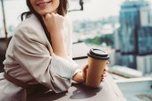 cropped view of smiling girl in beige suit posing on roof with coffee to go
