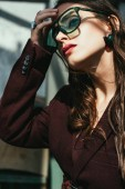 Fotografie fashionable woman posing in trendy burgundy suit and sunglasses on urban roof