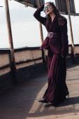stylová žena pózující v módním burgundském obleku a slunečních brýlích na městské střeše