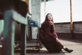 atraktivní elegantní dívka pózuje v módní burgundské oblek a sluneční brýle na městské střeše