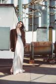 krásný elegantní model pózující v hedvábných šatech a hnědé bundy na střeše