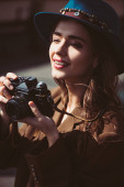 smiling woman in hat taking photos on vintage photo camera on roof