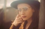 divatos nő pózol kalap, szemüveg és barna kabát a tetőn