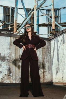 Attractive elegant model posing in trendy burgundy suit on urban roof stock vector