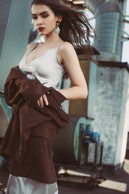 Beautiful elegant girl posing in silk dress and brown jacket on roof stock vector