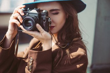 Attractive woman in hat taking photos on retro photo camera on roof stock vector