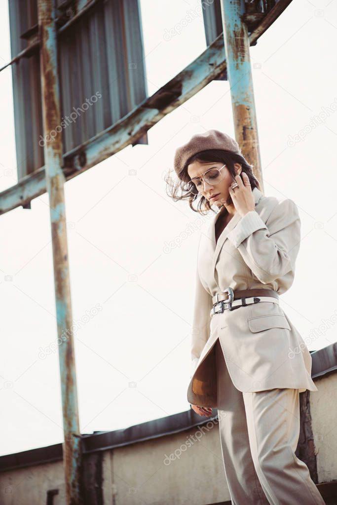 Attractive stylish woman posing in beige suit and beret on roof stock vector