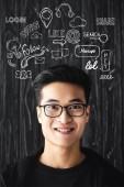 usmívající se asijský muž v brýlích při pohledu na kameru na dřevěném pozadí s ilustrací