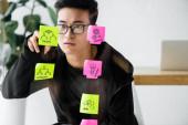 Asijský seo manažer psaní na lepicí poznámku s ilustrací