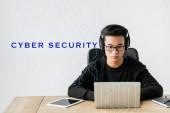 Asijský hacker pomocí notebooku a posezení v blízkosti ilustrace s kybernetickou bezpečností