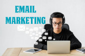 Photo asian seo manager using laptop and sitting near illustration with email icons and marketing lettering
