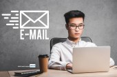 Photo asian seo manager using laptop and sitting near e-mail illustration