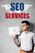 Photo asian seo manager holding paper with concept words of seo and standing near seo services illustration
