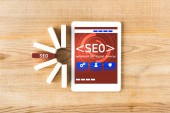 top view of wooden rectangles with lettering seo and digital tablet with illustration