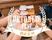 Ausgeschnittene Ansicht von multikulturellen Freunden, die in einer Kneipe mit Oktoberfest-Illustration Gläser mit Bier klappern