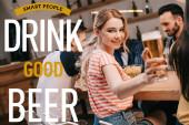 selektiver Fokus einer lächelnden jungen Frau, die in die Kamera blickt, während sie ein Glas helles Bier in der Nähe intelligenter Menschen hält, die gutes Bier trinken Illustration