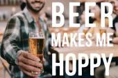 Der selektive Fokus eines Mannes, der ein Glas leichtes Bier in der Hand hält, während er mit Freunden in der Nähe von Bier in der Kneipe sitzt, macht mich munter Illustration