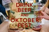 abgeschnittene Ansicht von Freunden, die Bier trinken und Snacks in der Kneipe mit Bier trinken und Oktoberfest Illustration