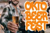 selektiver Fokus des Mannes mit einem Glas leichten Bieres, während er mit Freunden in der Nähe des Oktoberfests in der Kneipe sitzt Illustration