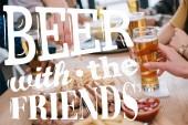 abgeschnittene Ansicht von Freunden, die Bier trinken und Snacks in der Kneipe essen