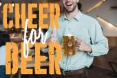 Ausgeschnittene Ansicht eines lächelnden jungen Mannes, der einen Becher Pils in der Hand hält und den Daumen in die Höhe reckt, um die Bier-Illustration zu bejubeln