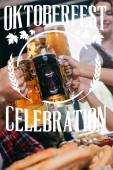 Teilansicht von Freunden, die helle und dunkle Bierkrüge mit Oktoberfest-Illustration klappern