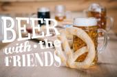 Draufsicht auf Bratwürste, Zwiebelringe, Pommes, Brezeln und Becher mit Bier auf Holztisch in Kneipe mit Bier mit den Freunden Abbildung