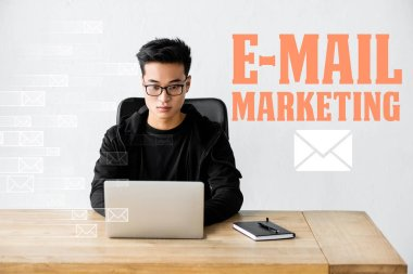 Asian seo manager using laptop and sitting near illustration with e-mail marketing illustration stock vector