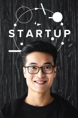 Smiling asian man in glasses looking at camera on wooden background with startup illustration stock vector