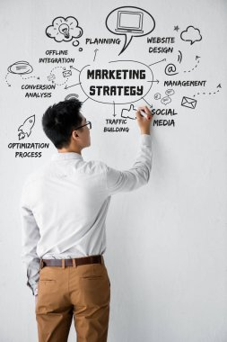 Back view of seo manager writing on wall with illustration with concept words of marketing strategy illustration stock vector