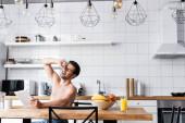 Hemdloser Mann lacht, während er digitales Tablet in der Küche mit Obst und Kaffee benutzt