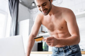 cheerful shirtless man shopping online with credit card and laptop on kitchen