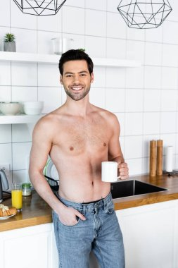 Smiling shirtless man holding cup of coffee on kitchen with breakfast stock vector