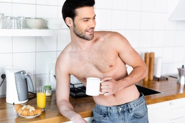 Cheerful shirtless man holding cup of coffee on kitchen with breakfast stock vector