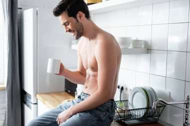 laughing shirtless man holding cup of coffee on kitchen in morning