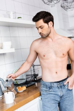 Shirtless man pouring coffee from pot into cup on kitchen stock vector