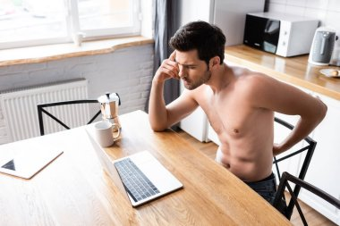 Thoughtful shirtless freelancer working on laptop on kitchen with coffee stock vector
