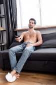 Photo smiling pensive shirtless man holding remote controller while watching tv at home
