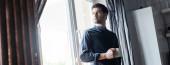 pohledný muž držící šálek kávy a stojící u okna doma v karanténě, horizontální koncept