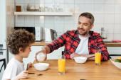 selektivní zaměření šťastný otec drží láhev s mlékem v blízkosti roztomilý syn, sklenice pomerančového džusu a mísa s kukuřičnými vločkami