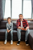 handsome father and curly son watching movie in living room