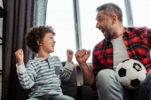 Photo cheerful kid and happy father holding football while looking at each other