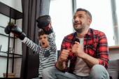 Glücklicher Mann schaut Meisterschaft neben emotionalem Sohn in Boxhandschuhen