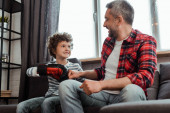 happy kid in boxing glove bumping fists with cheerful father in living room