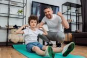 Photo happy father cheering near curly son showing muscle