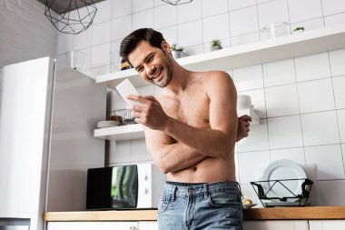 Sexy laughing man using smartphone in kitchen at home stock vector