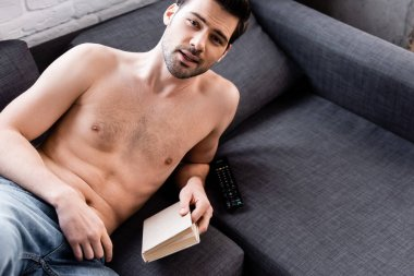 Sexy shirtless man holding book on sofa at home stock vector