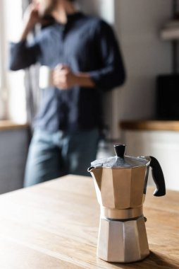 Cropped view of man holding cup of coffee and talking on cellphone on kitchen with coffee pot during quarantine, selective focus stock vector