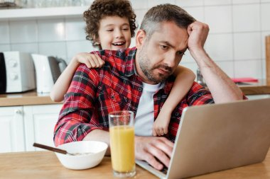 Mutlu oğlun seçici odağı evde çalışan yorgun serbest çalışan babaya dokunuyor.